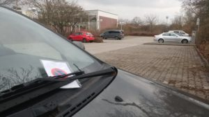 Strafzettel an Auto mit Parkplatz im Hintergrund